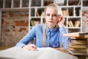 Female in blue shirt next to stack of books.