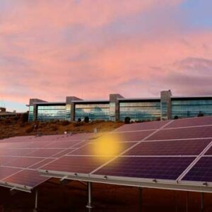 View of solar panels on top of a building under late afternoon sky.