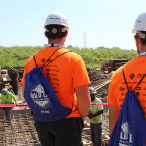 Students in hard hats looking at construction workers.